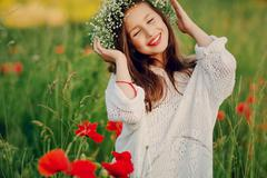 Beautiful little girl posing in a skirt   wreath of poppies Stock Photos
