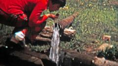 1972: Women drinking well drawn water from the end of a pipe. Stock Footage