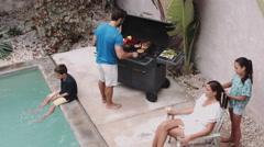 Family enjoying near swimming pool Stock Footage