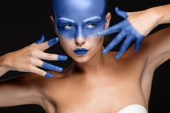 Portrait of a woman who is posing covered with blue paint - stock photo