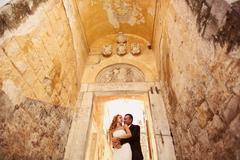 Bride and groom embracing near beautiful architecture - stock photo