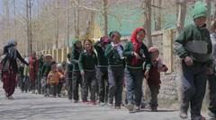 School children group walk through lane with trees,Kaza,Spiti,India Stock Footage