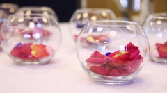 Transparent glass vases with flowers and rose petals Stock Footage