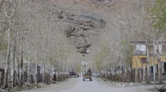 Tractor drives through lane with trees to camera,Kaza,Spiti,India Stock Footage