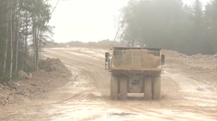 Open-pit dump truck rides away on the road Stock Footage