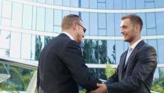 Old friends who have become successful businessmen, met near the office building Stock Footage