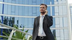 Successful businessman talking on the phone outside office building Stock Footage