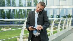 Young businessman talking on the phone drops a folder with documents - stock footage