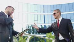 A chance meeting and a handshake of two business men near the office building - stock footage