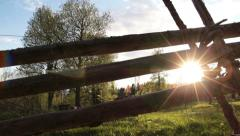 Wooden fence and meadow with trees in the background Stock Footage