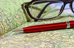 Ballpoint pen and glasses lie on geographical atlas - stock photo