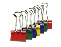 Binder clips colored on white background, shallow DOF Stock Photos