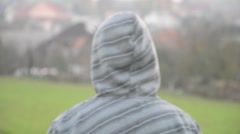 View from behind of young man walking with hooded sweatshirt - stock footage