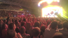 Excited young fans waving hands simultaneously. Fantastic light show flashing Stock Footage