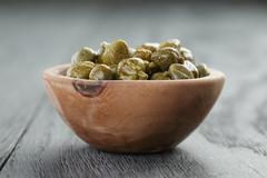 Marinated capers in olive bowl on wood table Stock Photos