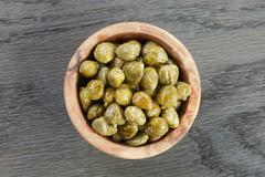 marinated capers in olive bowl on wood table - stock photo