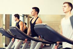 Group of men exercising on treadmill in gym Stock Photos