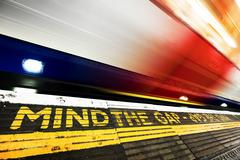 London underground. Mind the gap sign, train in motion. Stock Photos
