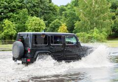 Car trying to drive against flood on the street in Gdansk, Poland. - stock photo
