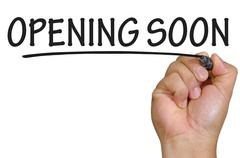 Stock Photo of hand writing opening soon