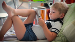 Little boy watching tales on tablet on bed Stock Footage
