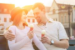 Stock Photo of Happiness couple with ice cream sitting at street under sunlight