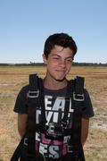 Young Teenager happy outdoors ready to go for skydiving - stock photo