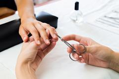 Manicurist trimming a clients cuticles - stock photo
