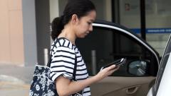 Asian girl using smart phone before getting on the car Arkistovideo