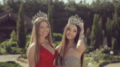 Two beautiful young girls in crowns and evening dresses posing in a green park Stock Footage