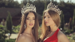 Two young winners of the beauty contest in the crown in the park Stock Footage