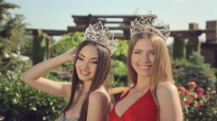 Two young beauty contest winner in long evening dresses and crowns in the garden Stock Footage