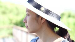 Asian woman enjoys herself in hot tropical nature holiday wearing summer hat Stock Footage