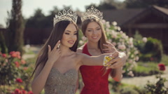 Two beautiful girls in evening gowns and crowns fooled around and doing selfie Stock Footage