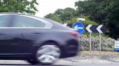 Cars pass in round about - England Stock Footage