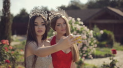 Two charming girls in evening gowns and crowns laughing and doing phone selfie Stock Footage