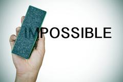 deleting the word impossible with an eraser - stock photo