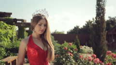 Lovely girl in a long red dress and with a crown on her head posing in the Stock Footage
