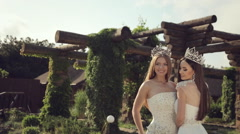 Portrait of two girls in wedding dresses and crowns outdoors in a park Stock Footage