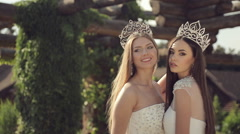 Shooting of two gorgeous girls in wedding dresses and crowns with precious Stock Footage