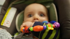 A baby sitting in a carseat playing with toy - stock footage