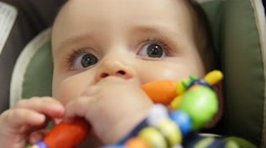 Baby sitting in a carseat playing with toy - stock footage