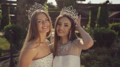 Beautiful girls wearing a crown and in white dresses cute smiling in the park Stock Footage