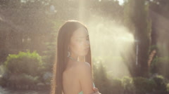 Sexy brunette in a swimsuit in the garden under spray of water Stock Footage