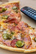 Pieces pizza in box with tv remote control Stock Photos