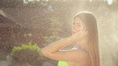 Beautiful young woman in jewelry in a bikini posing in the garden under spray of Stock Footage