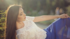 Beautiful model in a fashionable clothes lying on a stone and posing in the Stock Footage