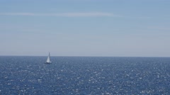 A sailboat traveling across the ocean skyline Stock Footage