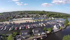 Aerial low fly over recreational harbor marina bungalows and boats 4k Stock Footage