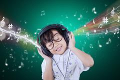 Adorable small girl enjoy music with headphones Kuvituskuvat